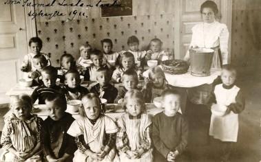 Porin suomalaisen kansanlastentarhan johtajatar Saima Kyhä ja lapset ruokailua aloittamassa.